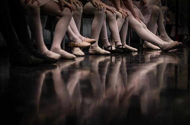 Baletky sedia na lavici vedľa seba s nohami na podlahe