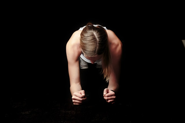 Žena podopretá na rukách cvičí