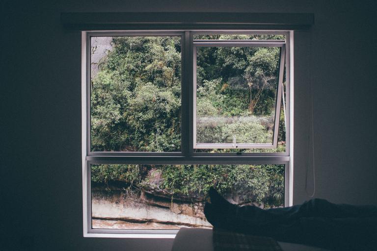 Hliníkové veľké okno na sivej stene, pri ktorom sedí človek s vyloženými nohami