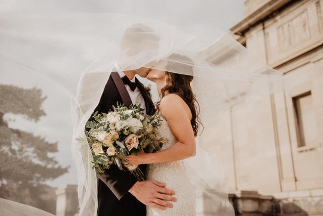 Ženích a nevesta s kyticou v ruke sa bozkávajú pod závojom.jpg