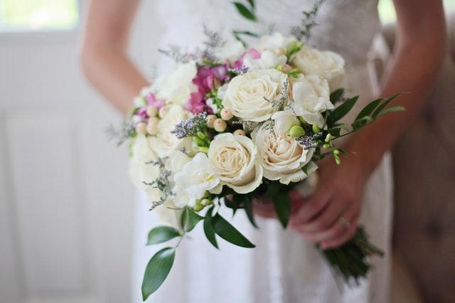 Nevesta drží v rukách kyticu z farebných kvetov.jpg