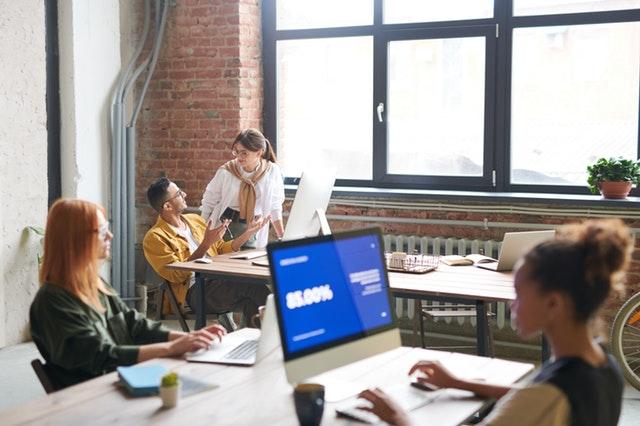 Ľudia v kancelárii s veľkým oknom sedia pri stoloch a počítačoch